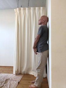 壁に寄り掛かって立ちます。